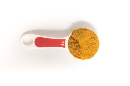 Curry Powder into a tablespoon. Measuring spoon on white background