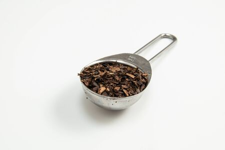 Toasted Erva-Mate into a measuring spoon on white background