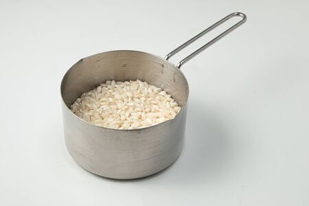 Half Cup of Arborio Rice on white background. Measuring Cup