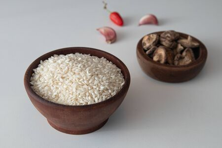 Arborio Rice in a wooden bowl on white background Archivio Fotografico