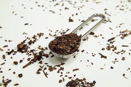 Teaspoon of toasted Erva-Mate Tea with lemon on white background