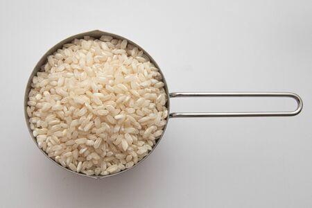 Arborio Rice in a measuring cup on white background Archivio Fotografico