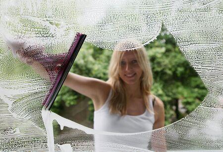 ruitenwisser: Vrouw reiniging van het venster, gericht op een glas  Stockfoto