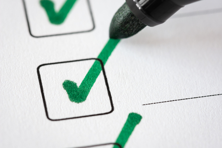 Checklist with marked checkboxes and pen