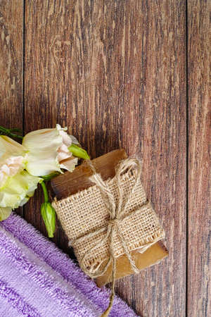 residual: Organic soap, purple sauna towel and flowers on walnut tree background, layout with free text space