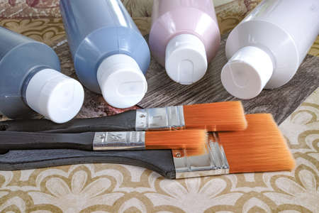 acrylic paint: Four bottles with acrylic paint and brushes on background with ornament, for hobby, drawing, home decoration, renovation Stock Photo
