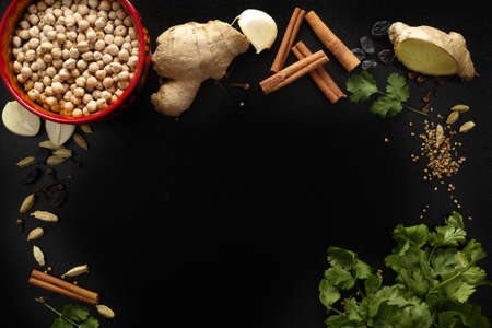 Indian spices, fresh coriander, ginger, garlic and dried cardamom, cloves, cinnamon on black background, copy space