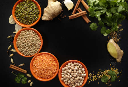 Indian spices, four bowls with pulse, legumes, fresh coriander, ginger, garlic and dried cardamom, cloves, cinnamon on black background, copy space Standard-Bild