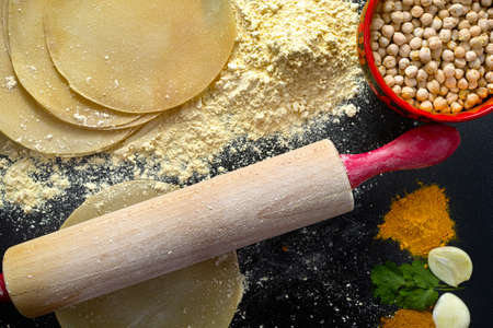 red gram: Papadums made from gram flour, bowl with chickpea, wooden rolling pin and indian spices Stock Photo