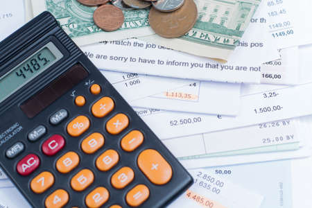 unpaid: Mortgage and utility bills, foreign coins and dollars banknotes, calculator, different amounts Stock Photo