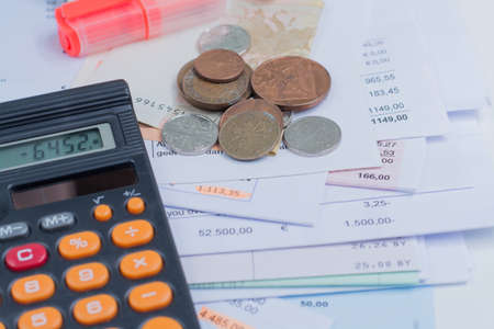moneyless: Mortgage and utility bills, foreign coins and dollars banknotes, calculator, different amounts Stock Photo