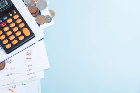 unpaid: Mortgage and utility bills, foreign coins and calculator, different amounts, copy space, on blue background Stock Photo