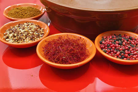 red food: Moroccan tahine with four bowles with spices saffron, pepper, ras el hanout on red background, delicious North African spicy food