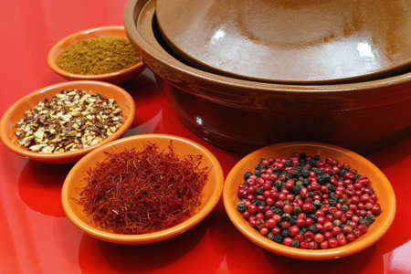 red background: Moroccan tahine with four bowles with saffron, ras el hanout, pepper on red background, delicious North African spicy food