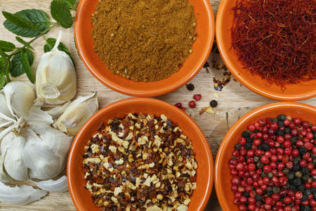 ras: Four bowles with saffron, pepper, ras en  hanout, fresh mint, garlic on teak wood table top Stock Photo