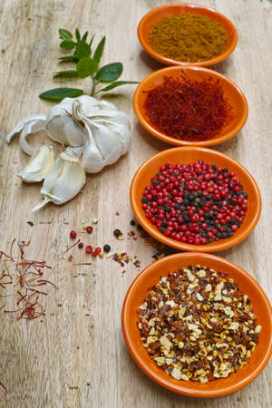ras: Four bowles with saffron, pepper, ras en  hanout, fresh mint on teak wood table top Stock Photo