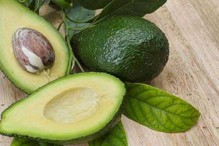 Fresh avocado with avocado leaves on teak wood table top