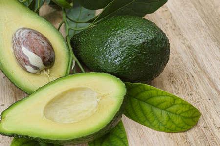Verse avocado met avocado bladeren op teak houten tafelblad
