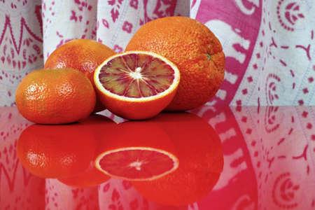 kitchen background: Various fresh citrus fruits, orange, blood orange, mandarin on red table top with reflection Stock Photo