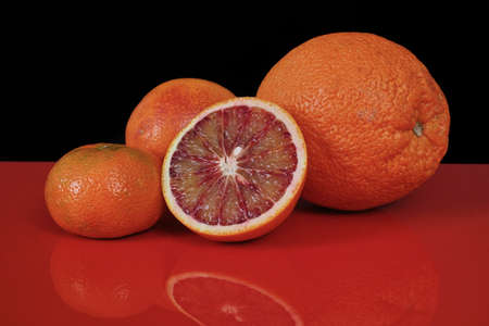 red food: Various fresh citrus fruits, orange, blood orange, mandarin on red table top and black background