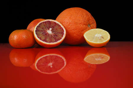 red food: Various fresh citrus fruits, orange, blood orange, mandarin, lemon on red table top with reflection and black background, copy space