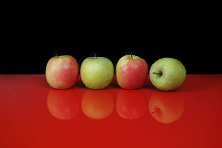 granny smith: Fresh Granny Smith and Pink lady apples on red table top with reflection and black background