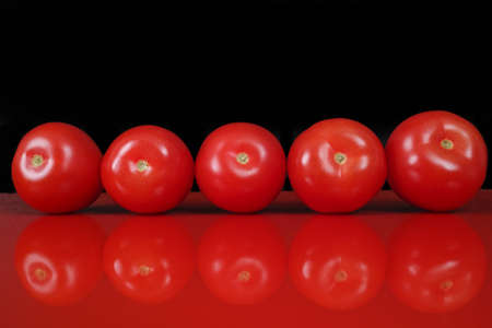 red food: Fresh red Roma tomatoes on red table  top with reflection and black background, copy space