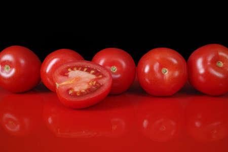 fondo rojo: Frescos tomates rojos gitanas en tapa de vector de color rojo con la reflexi�n y el fondo negro, copia espacio