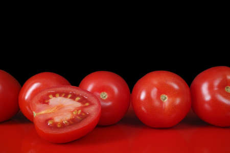 red background: Fresh red Roma tomatoes on red table  top and black background, copy space, closeup Stock Photo
