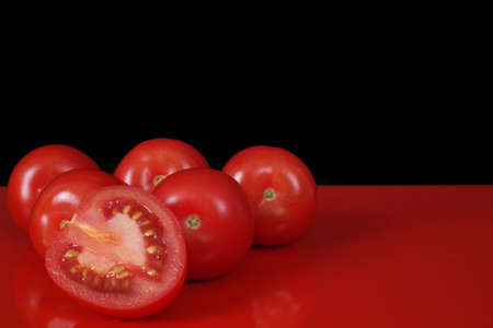 red food: Fresh red Roma tomatoes on red table  top and black background, copy space