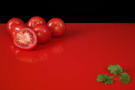 red  black: Fresh red Roma tomatoes and green coriander on red table  top with reflection and black background, copy space Stock Photo