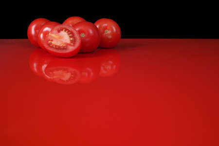 vegetable background: Fresh red Roma tomatoes on red table  top with reflection and black background, copy space