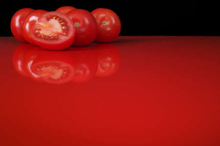 red  black: Fresh red Roma tomatoes on red table  top with reflection and black background, copy space
