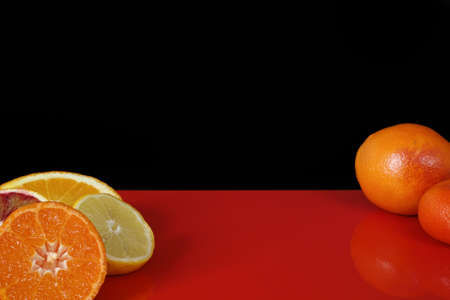 red  black: Various fresh citrus fruits, orange, blood orange, mandarin, lemon on red table top and black background, copy space