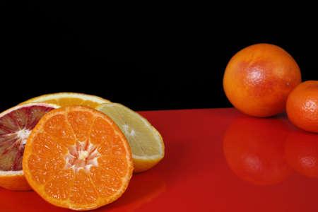 red background: Various fresh citrus fruits, orange, blood orange, mandarin, lemon on red table top and black background, copy space