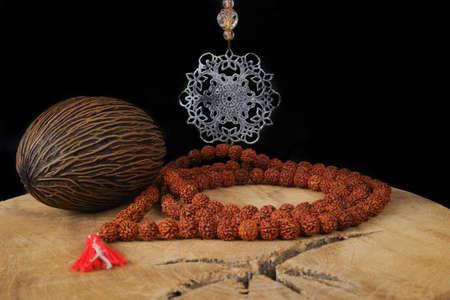 yogic: Indian art - tin mandala, prayer beards from Rudraksha, Foxtail palm seed on teak wood and black background Stock Photo