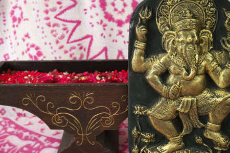 Indian spiritual art - golden Ganesha elephant, red candles on background with indian ornament