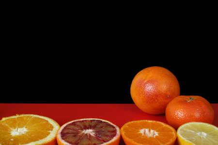 fondo rojo: Diversas frutas c�tricas, naranja, naranja sanguina, mandarina, lim�n en la superficie de la mesa de color rojo y fondo negro, copia espacio