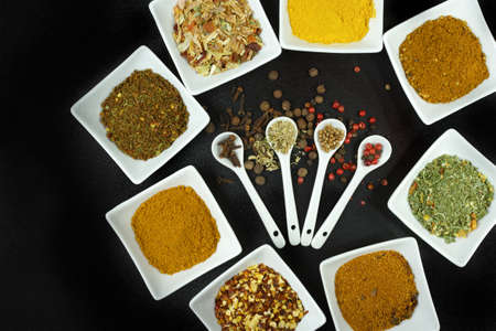 seasonings: Set of spices and seasonings, small ceramic white bowls and spoons on black background