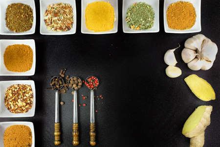 flavour: Set of spices and seasonings, small ceramic white bowls, vintage metal spoons on black background Stock Photo