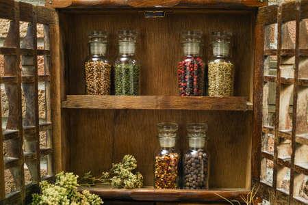 Farms vintage Kruidenrek of Storage Kast: Wall Mount - plat scherm, twee laden, Zes glazen flessen met oregano op landelijke achtergrond dorpsleven
