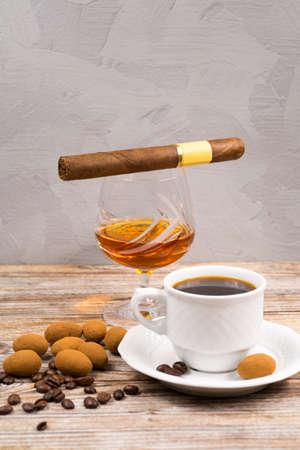 chocolate eggs: Cigar and  amber color brandy with cup espresso, coffee beans and chocolate eggs on wooden backdround