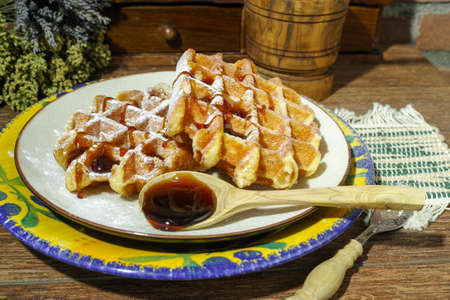 sugar powder: Handmade fresh belgian waffles with sugar powder and caramel syrop on rural wooden background Stock Photo