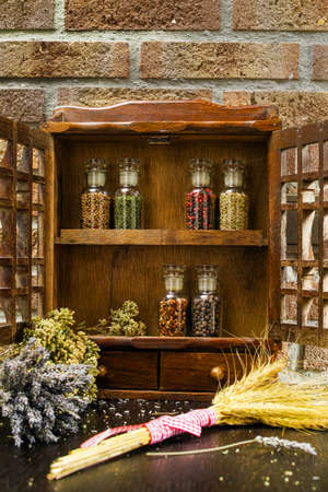 rack mount: Farms vintage Spice Rack or Storage Cabinet: Wall Mount - Display Shelf, Two Drawers, Six Glass Bottles with lavender, whole wheat and oregano on rural background village life Stock Photo