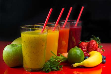Colorato fresco frutta pressato verde, giallo, oragne e succhi di frutta rossa con frutta fresca e bacche su sfondo nero e rosso