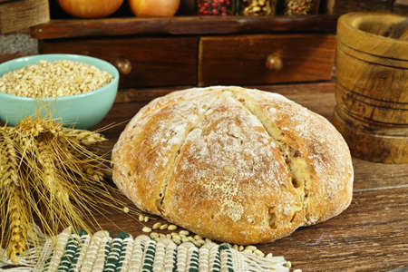 Round Loaf of Home made Bread with onion, whole wheat, in rural style on brick wall background
