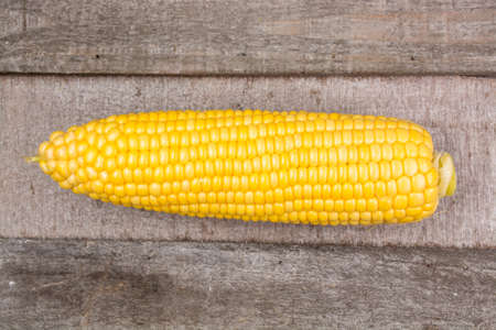 genetically modified crops: Fresh corn with leaves on wooden background