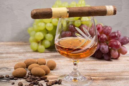chocolate eggs: Cigar and  amber color brandy with green and red fresh grape and chocolate eggs on wooden backdround Stock Photo