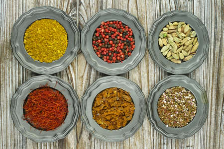 food additives: Spices and herbs in metal bowls. Food and cuisine ingredients. Colorful natural additives Stock Photo