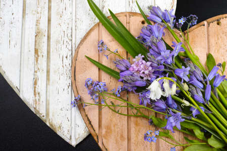 bunch of hearts: Bunch of fresh wild flowers hyacinths from the forest on wooden hearts
